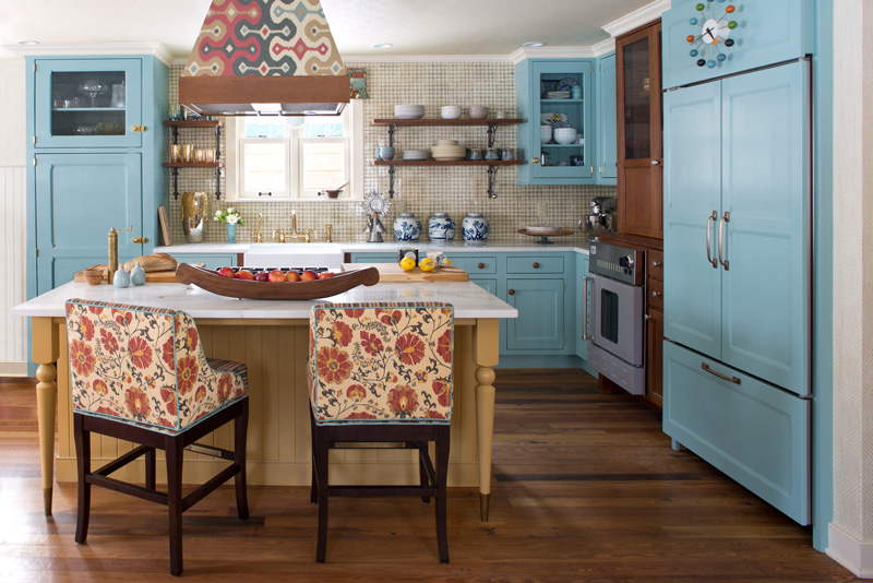 Beautiful interior design in kitchen with blue cabinets and patterned chairs at island