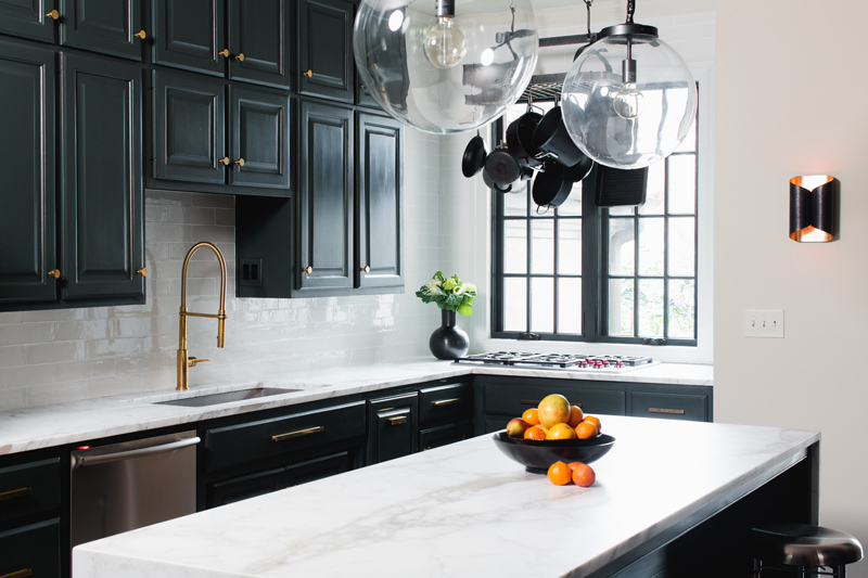 Beautiful interior design in kitchen with black cabinets and white marble countertops