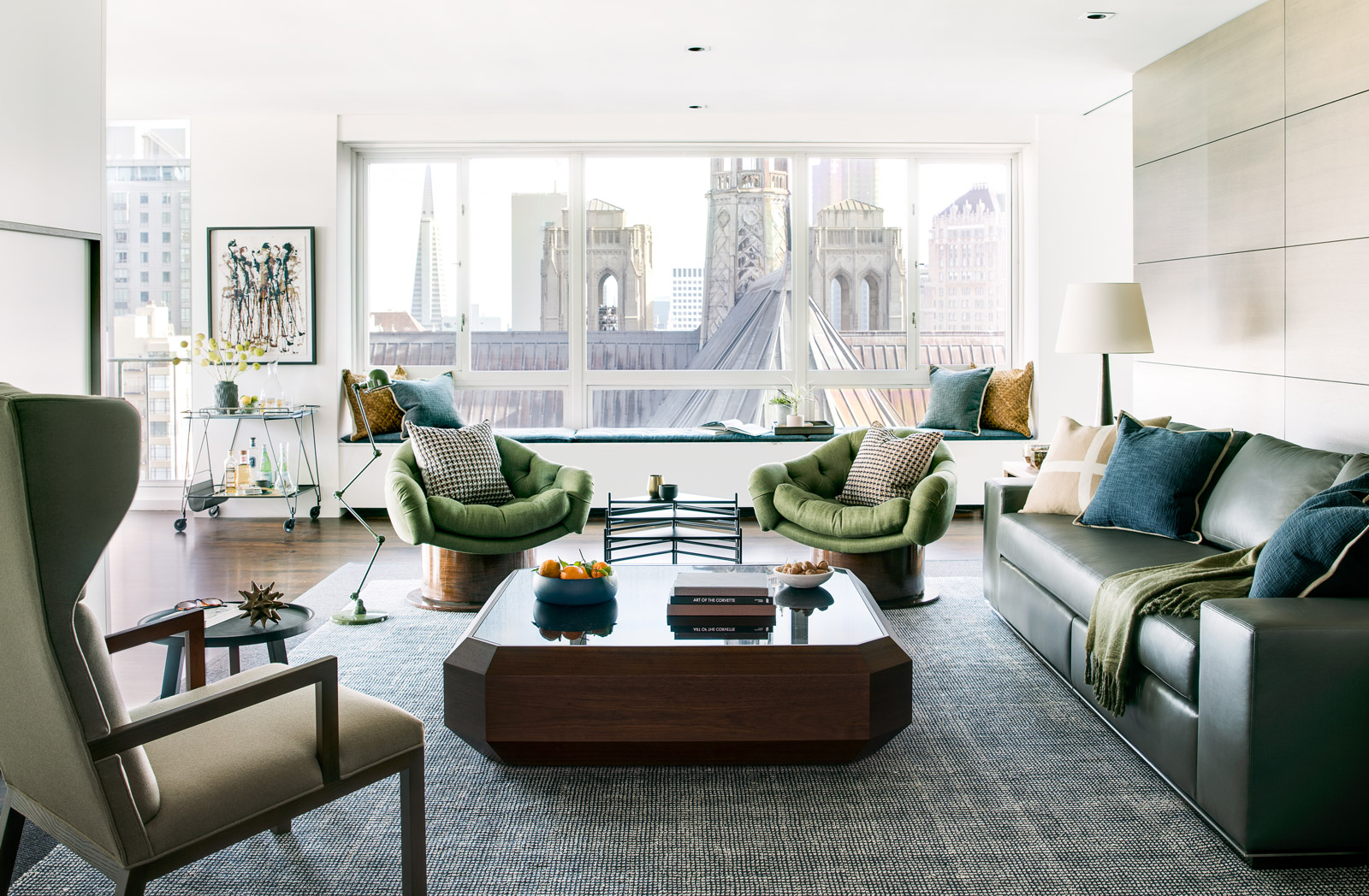 Beautiful interior design in high-rise living room with green leather couch and armchair seating
