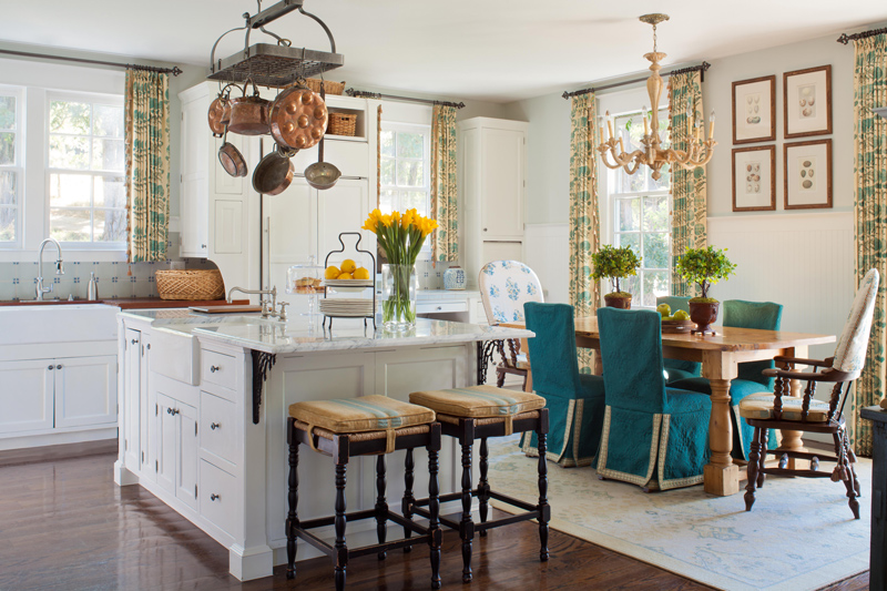 Beautiful interior design in open floor plan kitchen with island and teal chairs at wood dining table