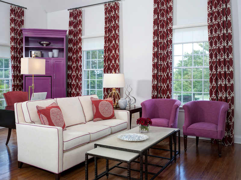 Beautiful interior design in living room with white couch, purple club chairs and maroon patterned curtains