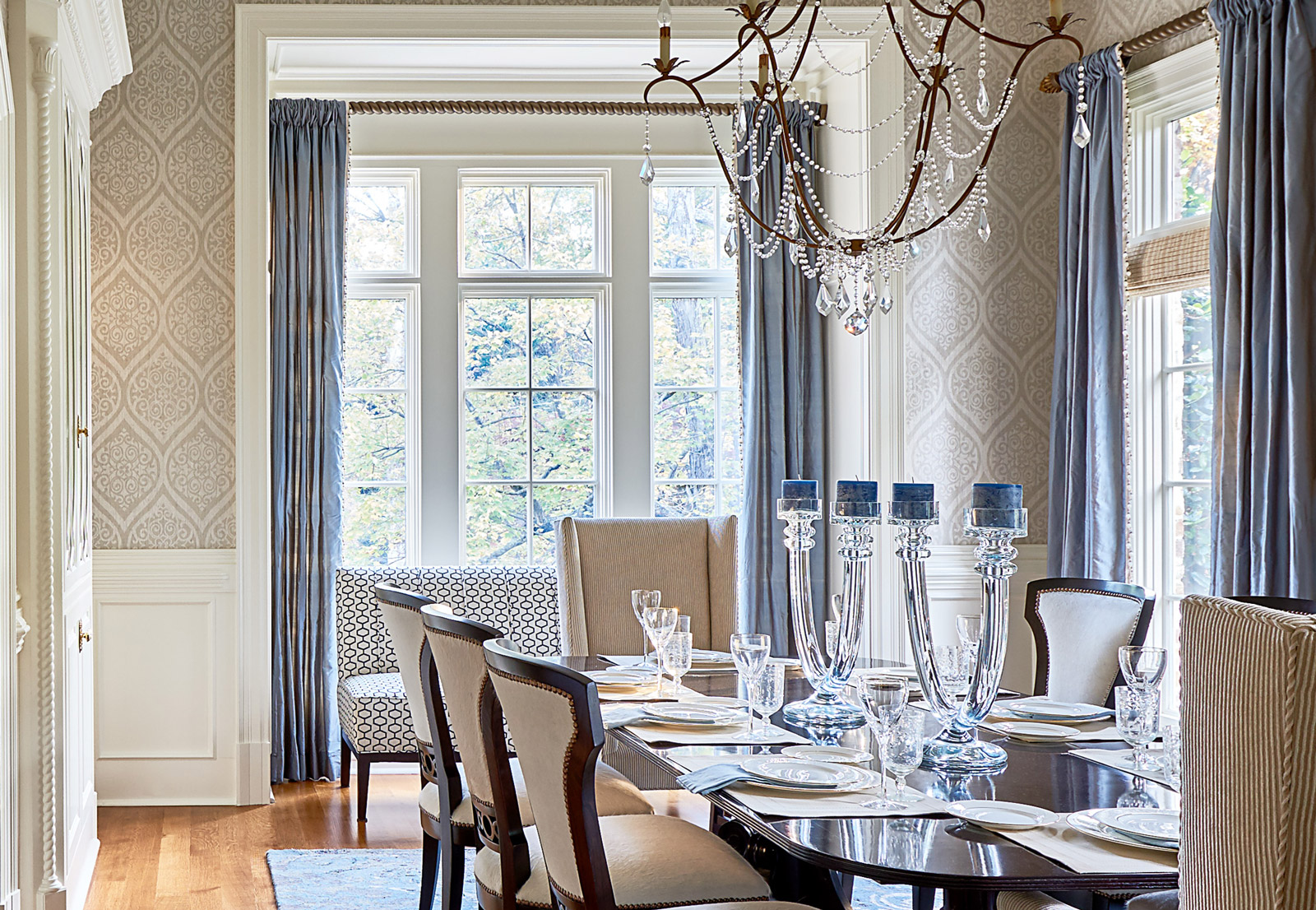 Beautiful interior design in formal dining room with crystal chandelier, beige seating and blue curtains