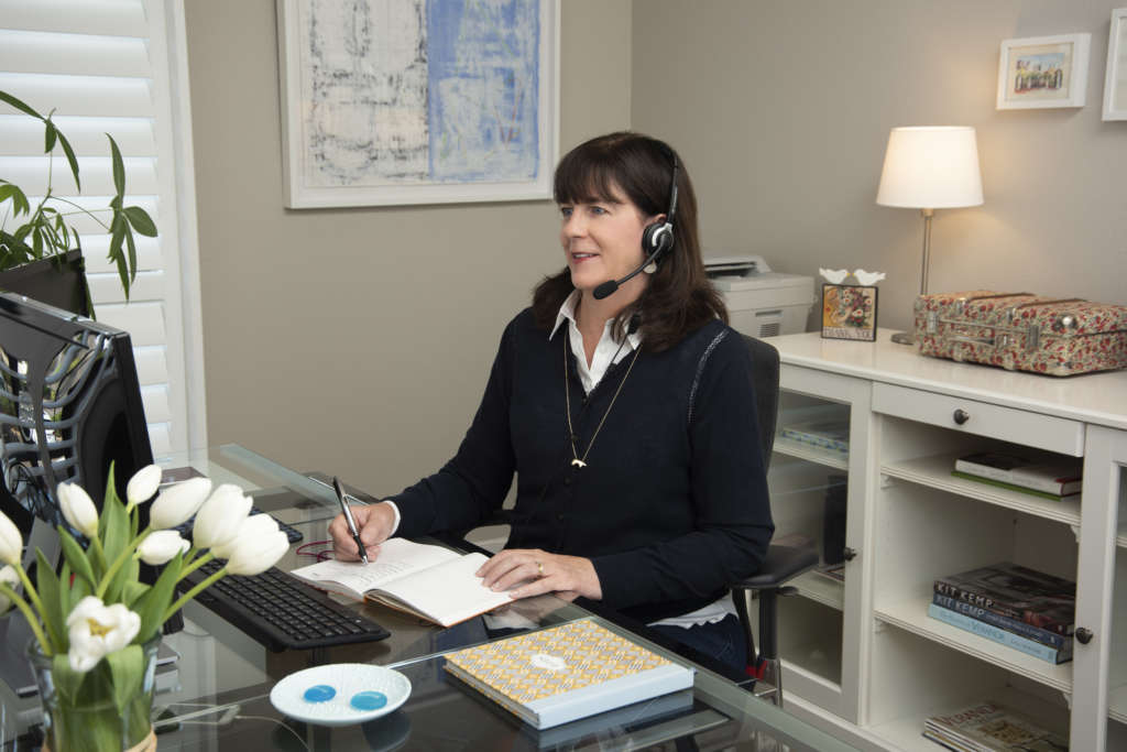 Monique Stemper taking calls at her desk at Stemper & Associates