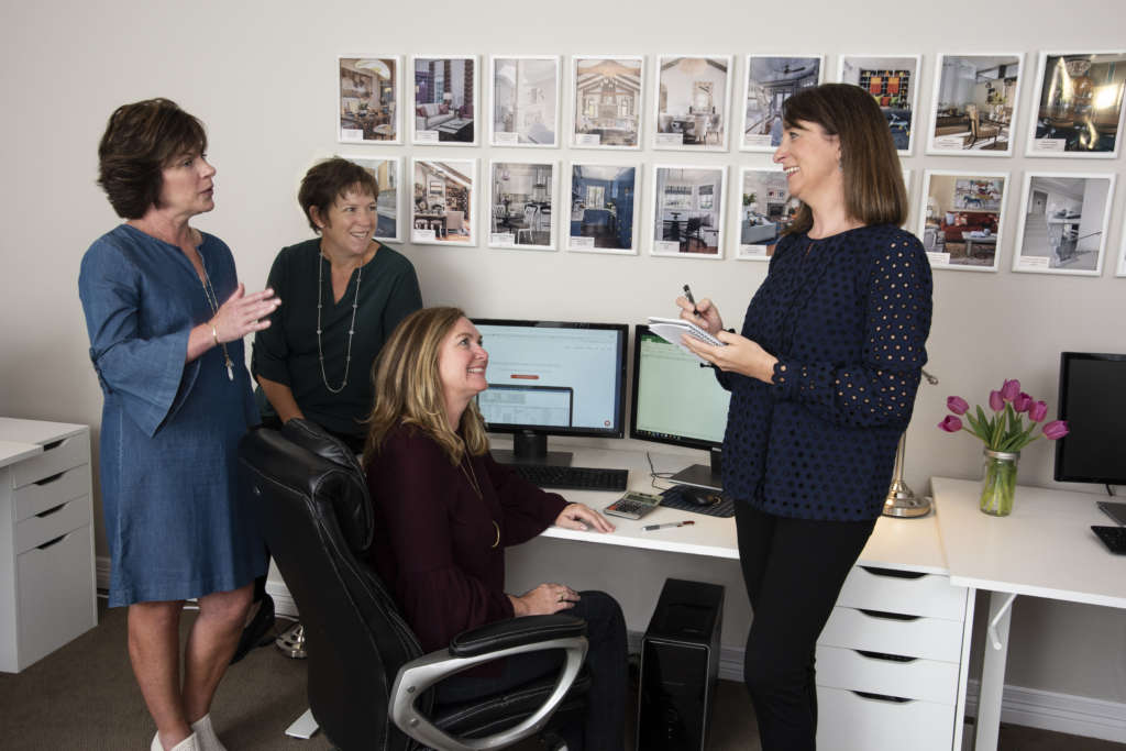 Four women collaborating near a computer at Stemper & Associates